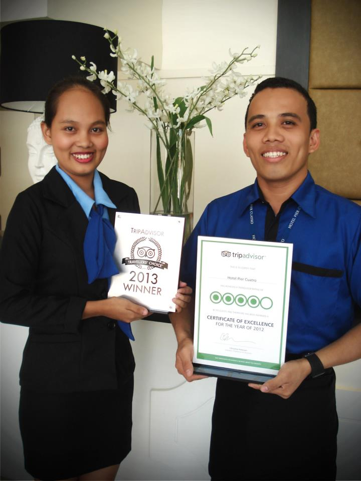 Ms. Jovie Robles and Mr. Lau Pino proudly holding Hotel Pier Cuatro's Awards